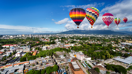 CHIANG MAI , THAILAND- SEPTEMBER 6, 2019 : High angle view of Colorful hot air balloons flying in bright sky day over Chiang Mai City, Thailand.