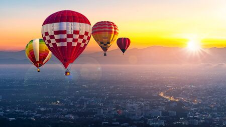 Chiang Mai, Doi Suthep in Thailand at sunrise -Landscape with hot air balloons flying over Chiang Mai City in sunlight and mist in the morning.