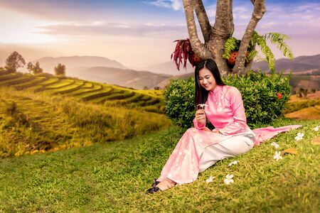 Beautiful Vietnamese Girl sitting on green lawn and golden terraced rice fields background.