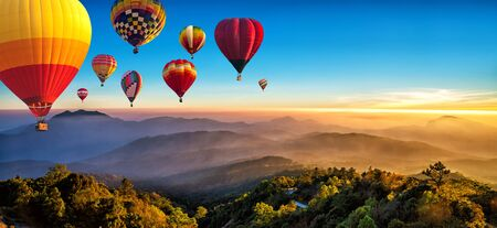 Hot air balloons flying over sea of mist awakening in a beautiful hills at sunrise in Chiang Mai, Thailand. Imagens - 131128212