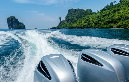 Splash wave water from Speed Boats Engines with Full Speed Drive on blue sea with beautiful sky and Chicken island in Krabi, Thailand.