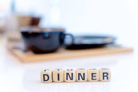 DINNER word written on wood cubes on table.