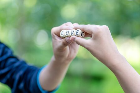 Man and woman hands holding wooden cubes with the word LOVE on green background. Relationship concept. Imagens - 131132306
