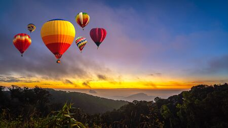 Colorful hot air balloons flying over Doi Inthanon National Park in sunrise time, Chiang Mai Province, Thailand.