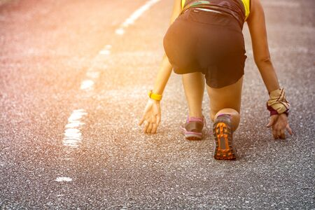 Athlete woman in running start pose on road closeup on shoe in the park. Imagens