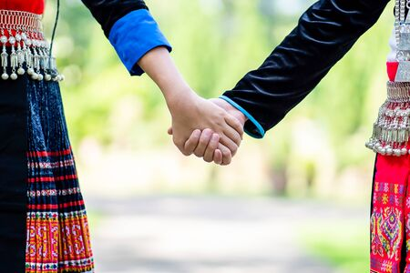 Happy young couple walking hand in hand and promised to take care of each other with love and caring. Lovers, Friendship and Valentine concept. Hmong couple. Imagens