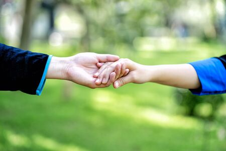 Couple hold hands in green field. Hand in hand, hand giving a helping hand. Imagens