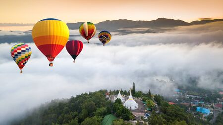 Colorful hot air balloons flying over Phra That Doi Kong Mu Temple at Mae Hong Son, Thailand. Imagens