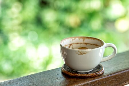 Empty coffee cup after drink on wood bacony and green nature bokeh background Imagens - 131133728