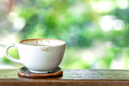 Empty coffee cup after drink on wood bacony and green nature bokeh background