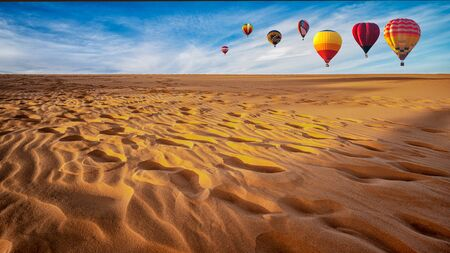 Colorful hot air balloons flying above the desert, Sand dunes. Travel and adventure concept Imagens