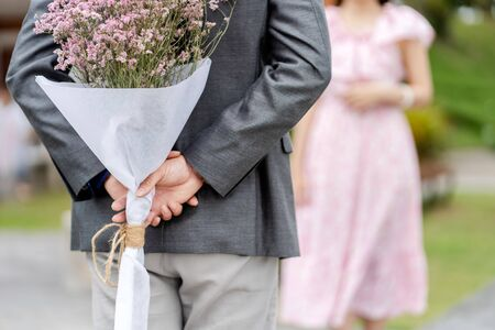 Young man is hiding flowers behind their backs to his girlfriend in the Park