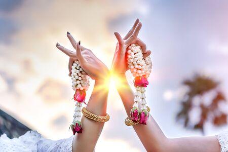 Women hands with jasmine garlands of Thailand Dancing art, Thai Classical Dance, (Ram thai) in evening light background