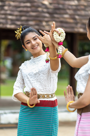 Young Thai woman of Thai Dancing with jasmine garlands in hands at old Thai Temple, Selective Focus