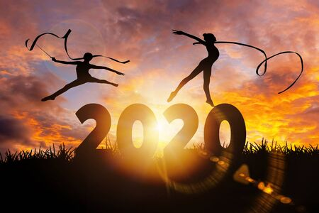 2020 New Year : Young gymnast woman dance ribbon silhouette performing rhythmic gymnastics on 2020 New Year, jumping doing split leap in the air, Happy new year concept Zdjęcie Seryjne