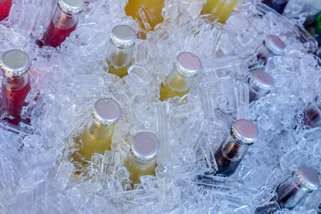 Cold glass beverages in heap of ice, beverage bottles on ice
