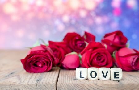 Love sign on wooden cubes and red roses flower on wooden table. Love and Valentine day concept.