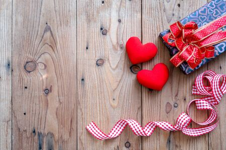 Valentines Day background with red heart shape, gift box and ribbon on wooden background