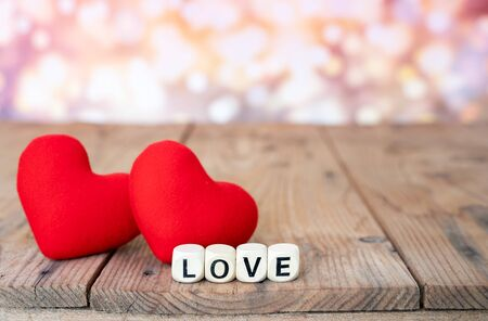 Love sign on wooden cubes and two red hearts on wooden table. Love and Valentine day concept. Stock fotó