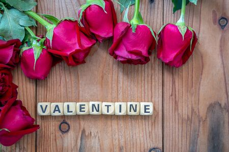 Valentine sign on wooden cubes and red roses flower on wooden table. Love and Valentine day concept.
