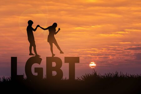 LGBT relationship concept. Silhouette of young lesbian couple holding hands at sunrise background to move forward together Stock fotó