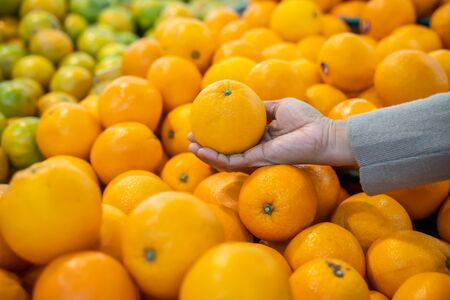 Woman hand choosing orange from the food counter at the supermarket. Shopping for fresh produce