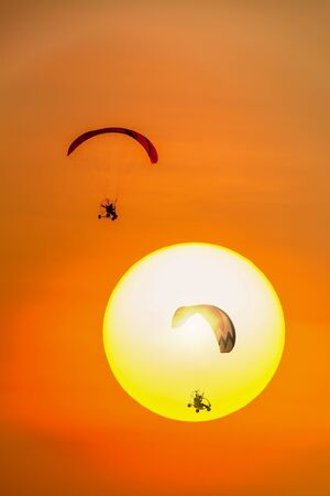 Silhouette group of Paramotors glider flying in the sun and orange sky Banque d'images