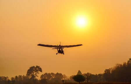 Ultralight trike flying with a pilot and a passenger against sunset sky, A microlight aircraft with two passengers with the sun