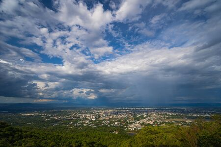 Beautiful panoramic aerial view of the city with dramatic rain and rainbow sky composite. Chiang Mai, Thailand.