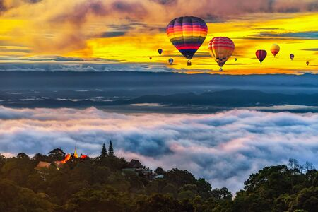 Hot air balloons flying over Wat Phra That Doi Suthep Temple with misty fog and sunlight, National Park in Chiang Mai Province, Thailand