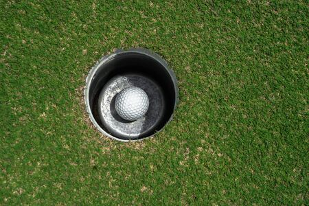 Golf ball in the hole at green golf course.