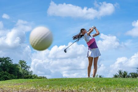 Golf ball just coming off the tee from girl golfer in swing in the morning time Imagens