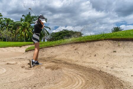 Side view of golfer female shooting golf ball from sand bunker. Golfer hitting golf ball with sand blast.