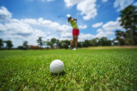 Golf girl player hitting ball on professional golf course.