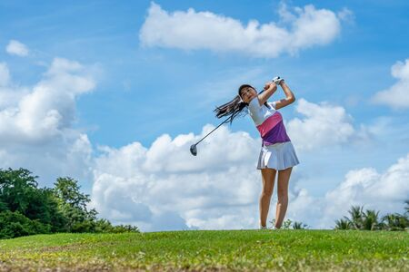 Gorgeous golfer lady hitting ball on professional golf course.