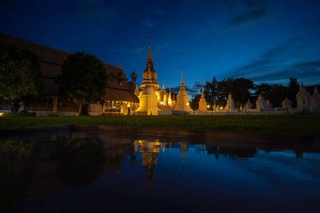 Wat Suan Dok Temple in twilight and reflection in Chiang Mai Thailand. Landmark of Chiang Mai.