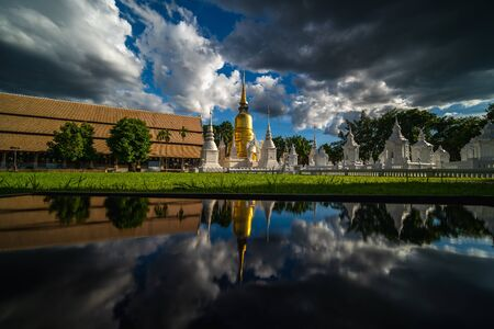 Wat Suan Dok Temple with rain clouds and reflection, is a Buddhist temple and Royal Temple of the Third Class in Chiang Mai  Thailand. Landmark of Chiang mai. Imagens