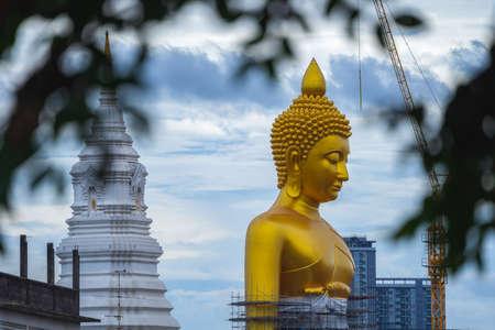 BANGKOK, THAILAND - JUNE 16, 2020 : The big golden buddha statue under construction seen from a distance at Khlong Bangkok Yai, Bangkok, Thailand