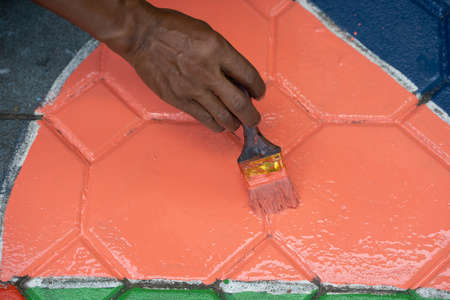Close-up Hand woman painting a floor with orange oil paint at home