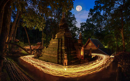 Lights from the candle lit at night around the church of Buddhist in Thailand Imagens