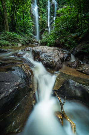 Tropical waterfall in rain forest at Mokfa Waterfall, Chiang Mai in North Thailand.