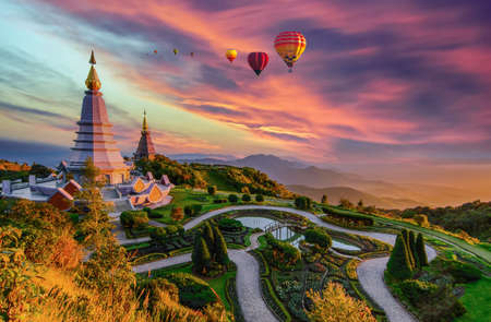 Colorful hot air balloons flying over two pagoda in Doi Inthanon Mountain in Chiang Mai, Thailand, Hot air balloon above high mountain at sunset Archivio Fotografico