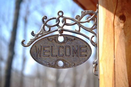 come in: Welcome sign on a log home porch