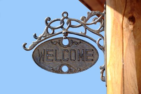 posting: Welcome sign on a porch surrounded by blue sky