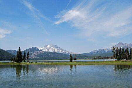 lichtrose witte wolken in een blauwe lucht boven de cascade pieken en een rustig meertje Stockfoto