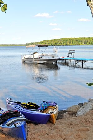 kajak en meer speelgoed op een serene meer in de buurt van een dok Stockfoto