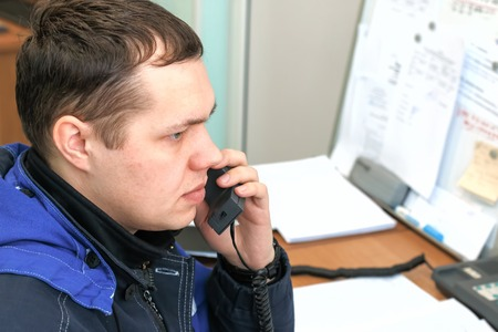 The dispatcher answers the phone. Young man in the workplace.