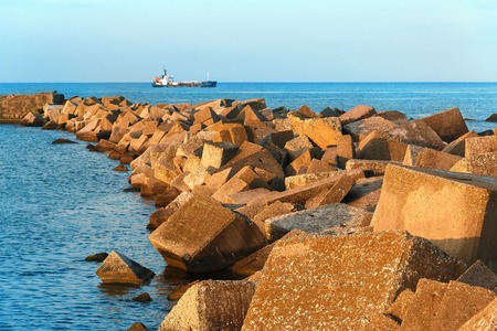 Fishing trawler in the sea. Guide lines of stones from the shore go into the horizon 免版税图像 - 113297006