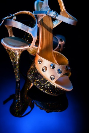 High-heeled shoes for dancing and striptease stand on a glass reflective surface. Champagne-colored shoes with round stones. Banque d'images