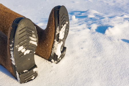 Human legs in warm felt shoes on the side of the snow.  Place to copy information about frostbite or accident in the winter in the cold. close-up Stock Photo